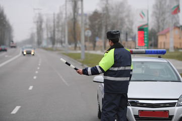 Police officer of the State Automobile Inspectorate controls traffic on city street