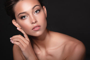 Portrait of a sophisticated young beautiful woman with clean tanned skin of face and body posing on a black background. The concept of beauty and salon procedures. Advertising space