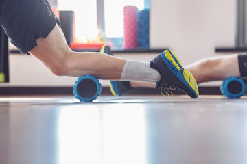 Two young purposeful men are training together with a sports roller in the gym. Sportsman doing foam roller exercises to relieve sore muscles. The concept of joint training and a healthy lifestyle