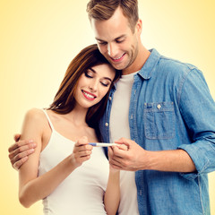 Square composition picture of young happy couple, finding out results of a pregnancy test
