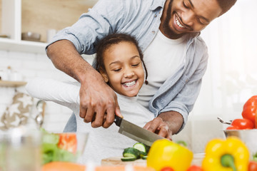 Cropped image of black father and dughter making salad