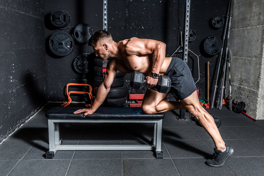 Back workout, Young sweaty muscular strong man doing workout training back muscles with dumbbell on the bench in the gym dark image real people