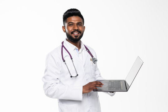 Portrait of a medical doctor standing in the studio while working with laptop, isolated on white background