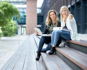 Arbeitskolleginnen mit Laptop beim Pausenkaffee in der Kaffeepause oder Mittagspause, bei einer Besprechung vor Ort