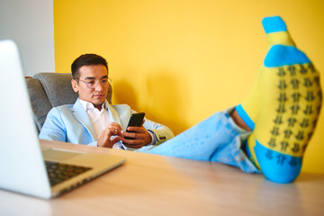 Handsome Asian businessman in suit with funny socks and glasses put his feet on the table, works in the office, successful Kazakh manager solves business issues by mobile phone