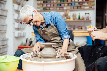 Senior woman spinning clay on a wheel with teacher at pottery class Fototapete