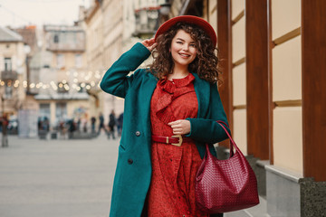 Happy smiling fashionable curvy woman wearing trendy autumn outfit: orange hat, snakeskin print dress, belt, green coat, holding red wicker leather bag, posing in street of European city. Copy space