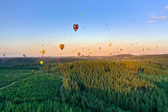 Colorful hot air balloons in different shapes fly over the forest. It is a coniferous forest in the Sauerland. The sun is almost setting, the sky is blue. Aerial shot.