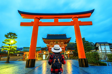 Wall Mural - Woman traveler with backpack at fushimi inari taisha shrine in Kyoto, Japan.