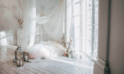 a large clean bright room with a window of white wooden floor, a mattress-bed, decorated with...