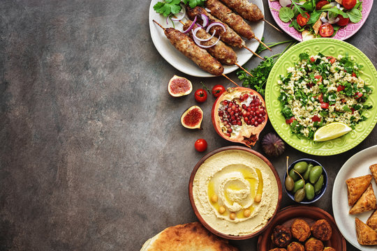 Arabic and Middle Eastern dinner table. Hummus, tabbouleh salad, Fattoush salad, pita, meat kebab, falafel, baklava, pomegranate. Set of Arabian dishes.Top view, copy space