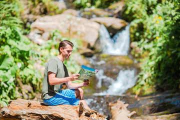 Man enjoying view of waterfall in gungle
