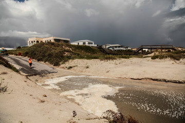 A man takes a picture on the dunes of the closed Crescent Beach before Hurricane Dorian in St. Augustine