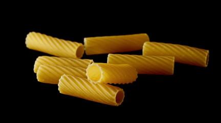 Pasta tubes, tortiglioni or elicoidali isolated on black background