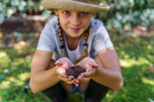 Beautiful little caucasian with hands full with ecological manure. Healthy family lifestyle. Ecological green values.