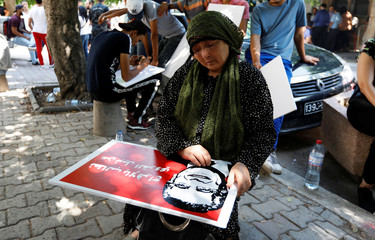 A women looks at a picture of a presidential candidate Nabil Karoui in front of the courthouse, in Tunis