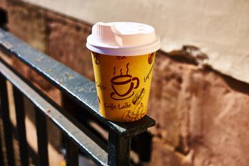 Coffee-To-Go Becher mit Banderole auf einem weißen Tisch zur Verdeutlichung von Plastikabfall