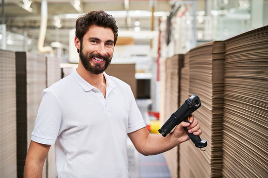 Portrait of smiling man in factory hall with barcode scanner