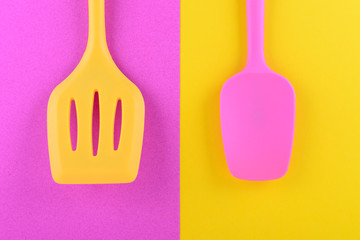 bright kitchen utensils on yellow and pink background, creative idea