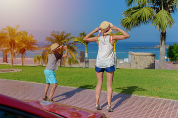Mother and son travelling by car jump together against beach and holding sunhats on summer vacation. Back view.