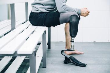 Athlete man with prosthetic leg sitting in gym locker room
