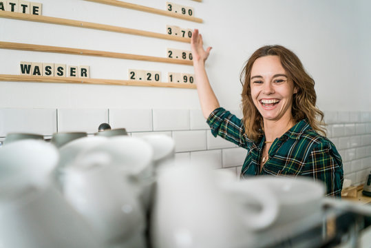 Proud young woman working in her own coffee shop