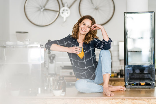 Young woman sitting barefoot on counter of her own coffee shop, drinking coffee