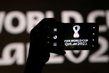 A man takes a picture of the tournament's official logo for the 2022 Qatar World Cup as displayed on the wall of amphitheater, in Doha