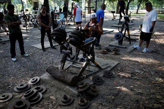 A man lifts weights made of rusty cars parts in a handmade gym made with construction bars, cement, and other recycled materials in Caracas