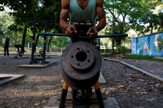 A man lifts weights made of rusty car parts in a hand made gym made with construction bars, cement, and other recycled materials in Caracas