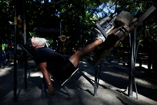 A man rests as he lifts weights in a handmade gym made with construction bars, cement, and other recycled materials in Caracas
