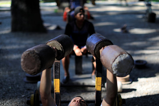 A man lifts weights made of cement in a hand made gym made with construction bars, rusty car parts, and other recycled materials in Caracas