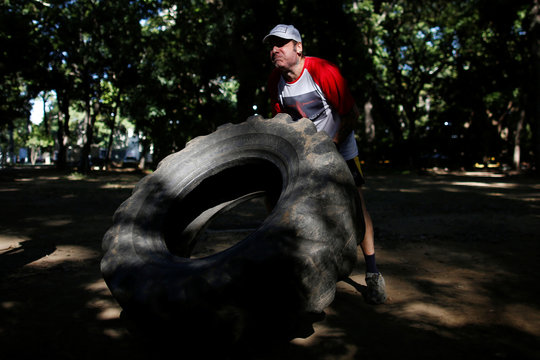 A man lifts a tractor tyre in a hand made gym made with construction bars, rusty car parts , and other recycled materials in Caracas