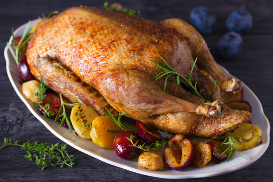 Whole duck with potatoes, plums and herbs
