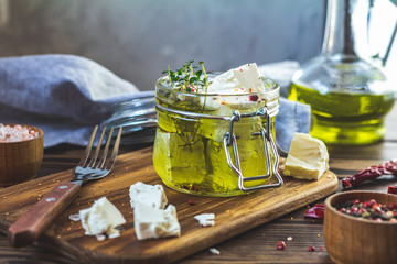 Feta cheese marinated in olive oil with fresh herbs in glass jar. Wooden background.