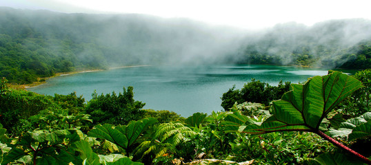 The turquoise green lagoon of Botos, in the Poas Volcano, Costa Rica, is surrounded by lush tropical vegetation.