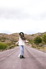 .happy woman with sombero dancing in the middle of an empty road in a rural area