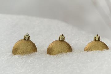 Three sparkling golden christmas balls lies in winter white snow. There is a place for text.
