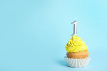 Birthday cupcake with number one candle on blue background, space for text
