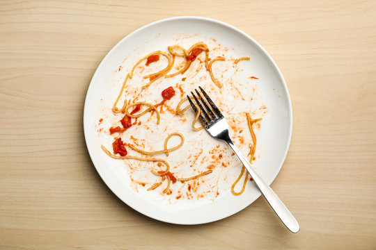 Dirty plate with food leftovers and fork on wooden background, top view
