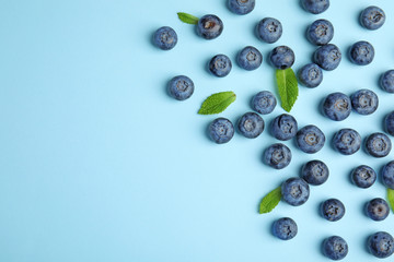 Tasty ripe blueberries and leaves on blue background, flat lay with space for text