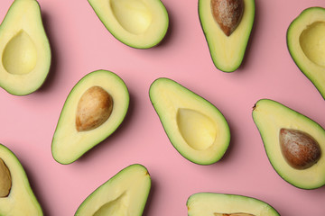 Cut fresh ripe avocados on pink background, flat lay