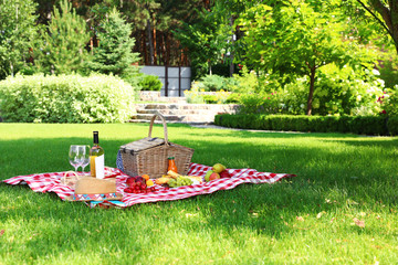 Aluminium Prints Picnic Picnic basket with products and bottle of wine on checkered blanket in garden. Space for text