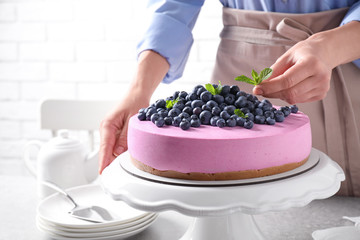 Young woman decorating tasty blueberry cake with mint at table, closeup