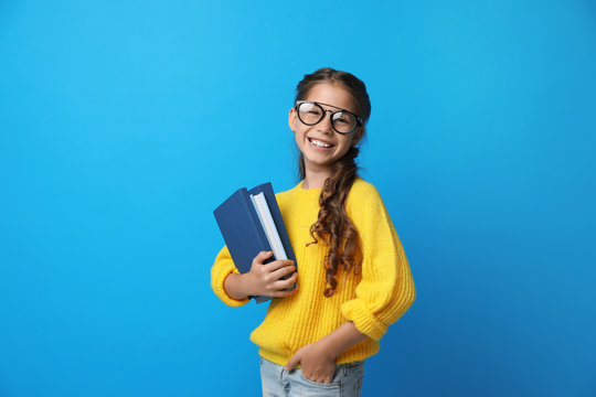 Cute little girl with glasses and books on blue background. Reading concept