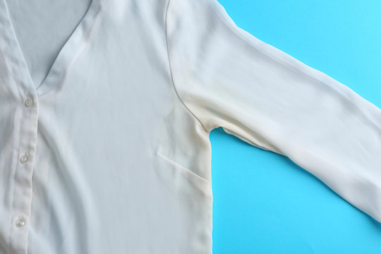 Clothes with deodorant stain on light blue background, top view