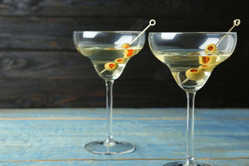 Glasses of Classic Dry Martini with olives on light blue wooden table against dark background