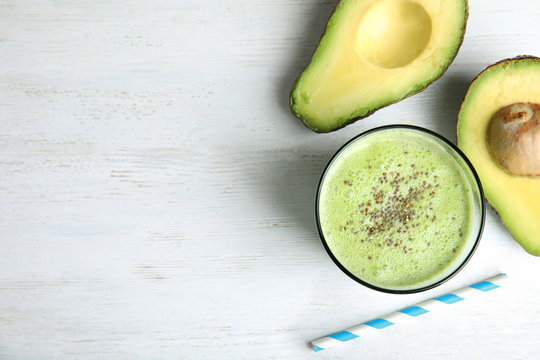 Glass of tasty smoothie with chia seeds and avocado on white wooden table, flat lay. Space for text