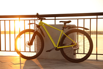 Yellow bicycle parked near railing on city waterfront at sunset