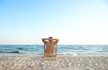 Fototapeta Young man relaxing in deck chair on beach near sea obraz